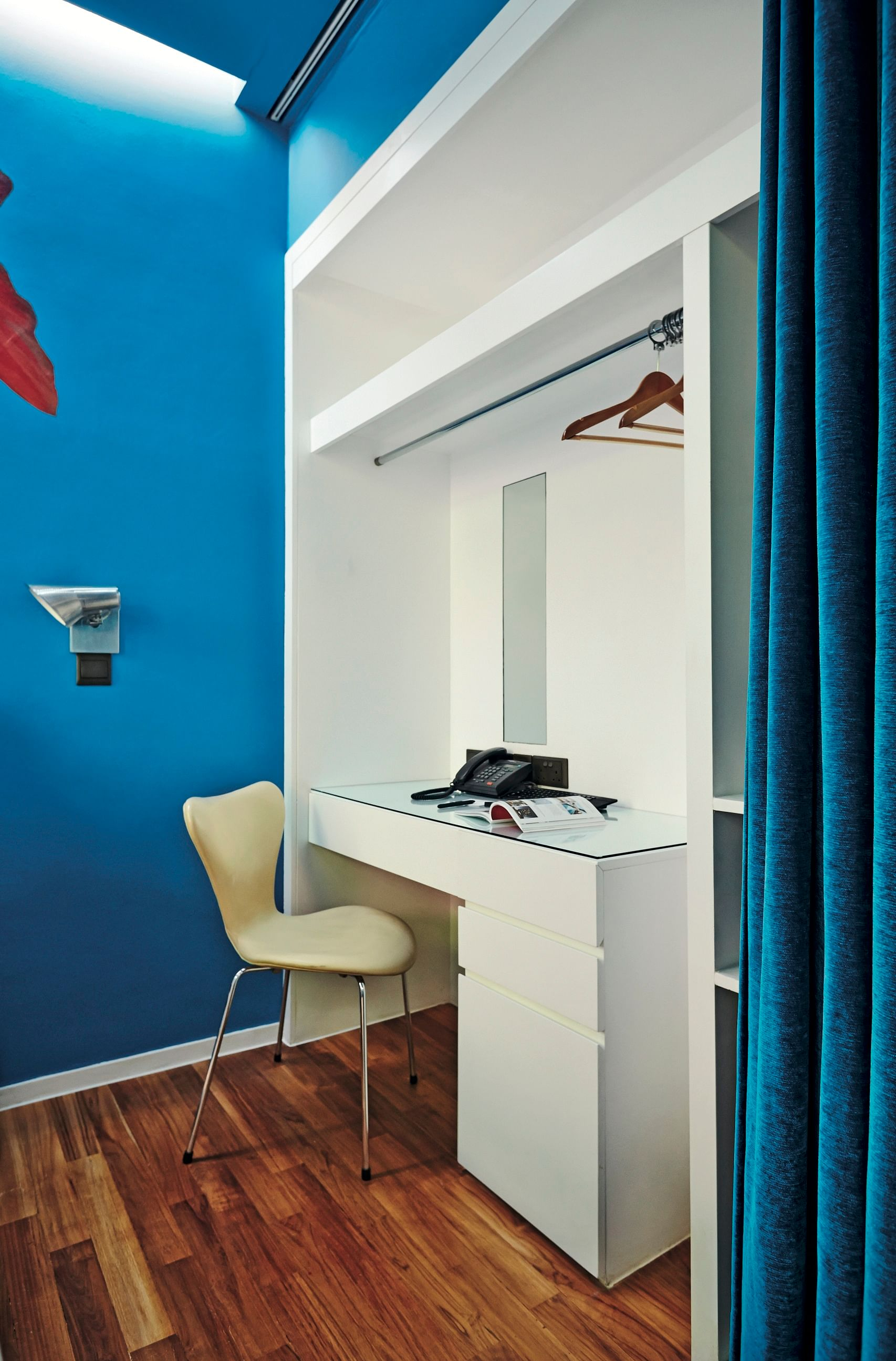 the wardrobe has a builtin tabletop and drawers that can be used as a workspace or dressing table and is easily concealed behind the curtain