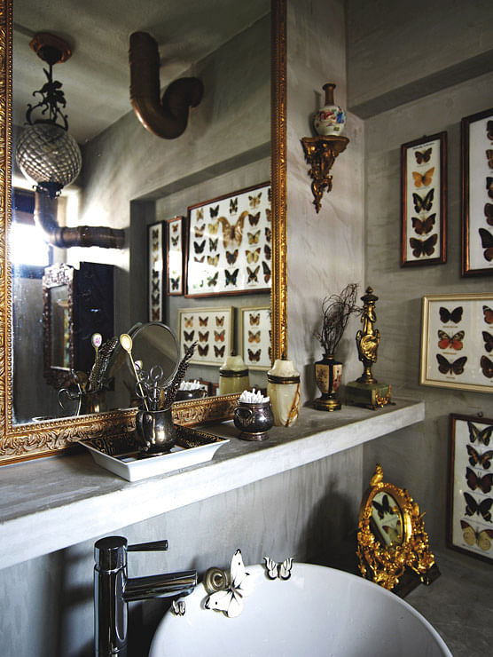 The Large Glided Mirror Above The Sink Visually Expands The Space. The  Brass Knick Knacks Dress Up The Stark Concrete Setting.
