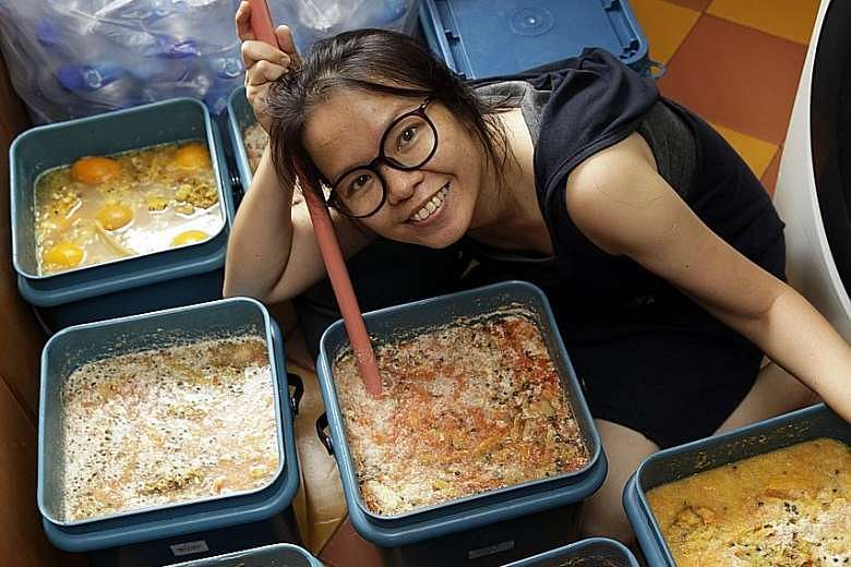 Volunteer Ng Wai Sen with her homemade garbage enzymes she uses for cleaning purposes.PHOTO: GIN TAY FOR THE STRAITS TIMES