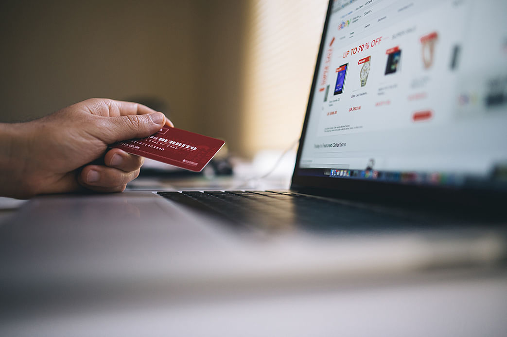 guy holding credit card and online shopping