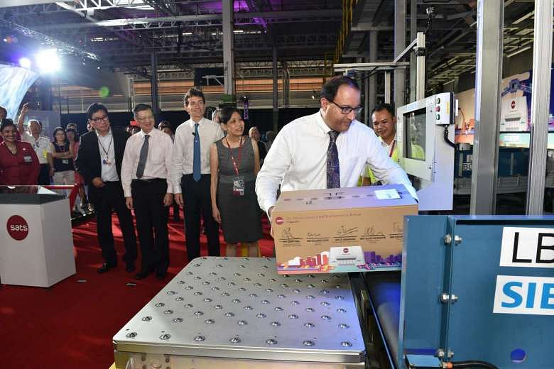 Trade and Industry (Industry) Minister S. Iswaran placing a parcel in the in-feed station at the new Sats e-Commerce AirHub